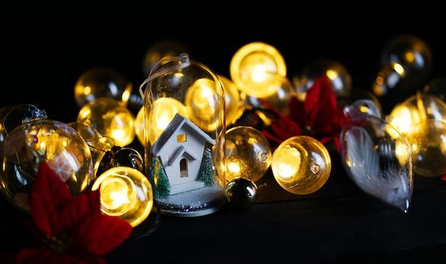Casa blanca de decoración navideña dentro de vidrio entre bombilla y flor de pascua roja