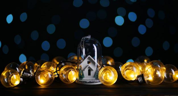 Casa blanca dentro del vidrio entre la bombilla, fondo azul bokeh oscuro
