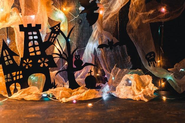 La casa de la bruja con una tumba y un árbol aterrador tallado en papel negro en una pared de madera con una telaraña y guirnalda led.