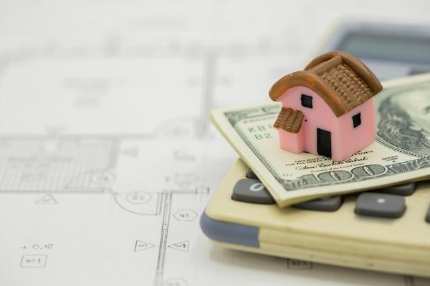 Casa en la calculadora con billetes de un dólar