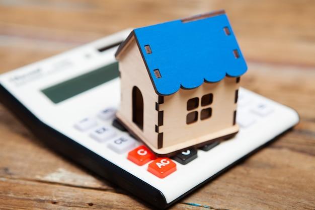 Casa y calculadora en una mesa de madera. calcular los costos de la casa