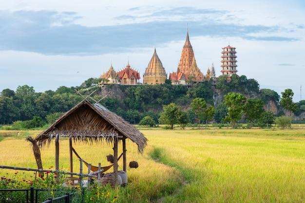 Casa de campo en el campo de arroz con la iglesia de wat tham sua en la colina