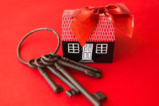 Casa de cartón con arco cerca de viejo manojo de llaves