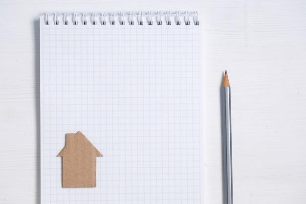 Casa de cartón en la hoja en blanco del cuaderno espiral, lápiz en blanco.