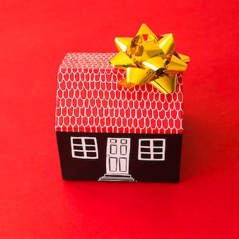 Casa de cartón de juguete con lazo.