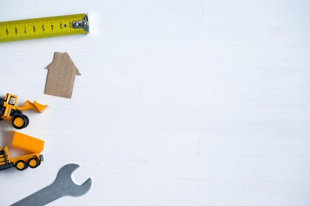 Casa de cartón, llave inglesa, ruleta, excavadora de juguete, camión en blanco con copyspace.