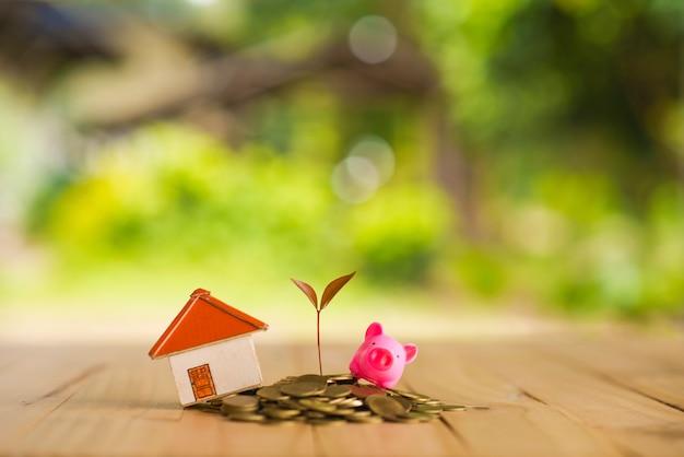 Casa colocada en monedas la mano de los hombres está planeando dinero de ahorros de monedas para comprar un concepto de concepto de vivienda para la escalera de propiedad, la hipoteca y la inversión inmobiliaria. para el ahorro o la inversión para una casa,