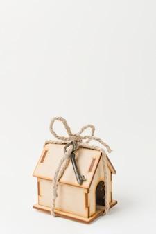 Casa como regalo con llave vintage sobre superficie blanca.
