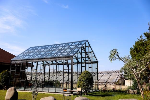 Casa de cristal transparente bajo el cielo azul