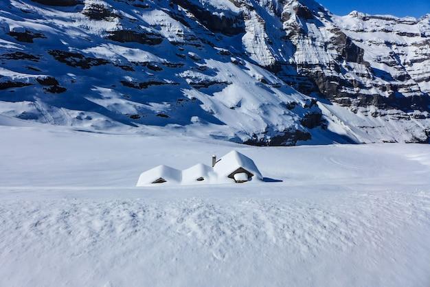 La casa está cubierta de nieve en el fondo de la montaña.