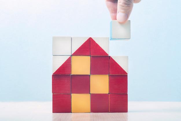 Casa de cubos. en un cuadrado de cubos, el mosaico presentaba una casa. la mano pone el último dado en el mosaico. concepto de negocio de construcción, éxito empresarial, concepto de negocio.