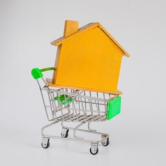 Casa dorada con carrito de compras, concepto de vivienda y bienes raíces.