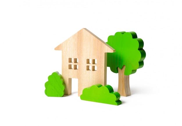 Casa de dos pisos rodeada de arbustos y árboles.
