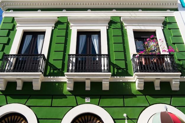 Casa de edificio residencial verde con valla de balcón de hierro negro y puertas con ventanas día soleado