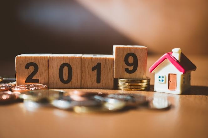 Casa en miniatura con número de bloque de madera de año nuevo y monedas de pila