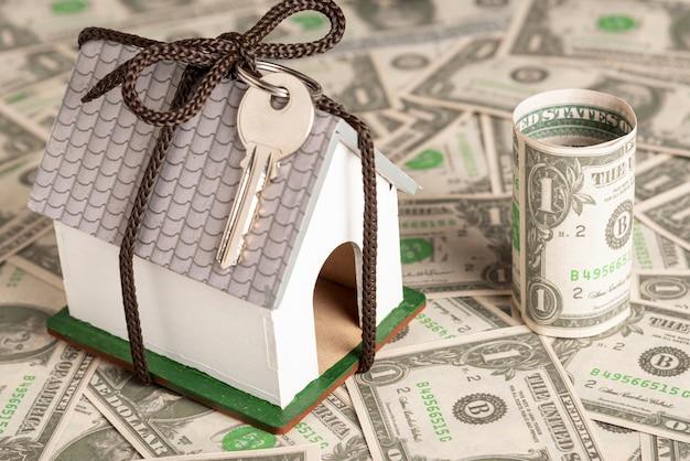 Casa envuelta con llaves sobre fondo de dinero