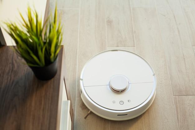 Casa inteligente. el robot aspirador funciona en un piso de madera en una sala de estar