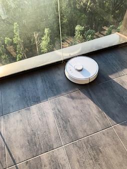 Casa inteligente. el robot aspirador funciona en el piso de una sala de estar.