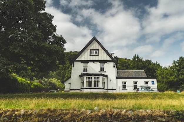 Casa irlandesa tradicional blanca entre árboles, campos.