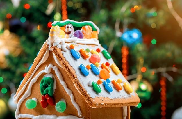 Casa de jengibre decorada en la superficie del árbol de navidad