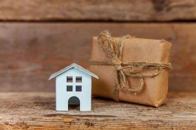 Casa de juguete blanco en miniatura y caja de regalo envuelta en papel artesanal sobre fondo de madera vieja
