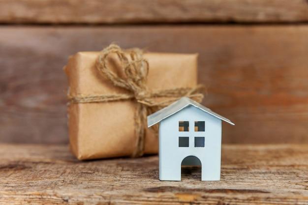 Casa de juguete blanco miniatura y caja de regalo sobre fondo de madera