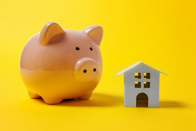 Casa de juguete blanco en miniatura y hucha sobre fondo amarillo