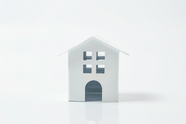 Casa de juguete blanco miniatura sobre fondo blanco.