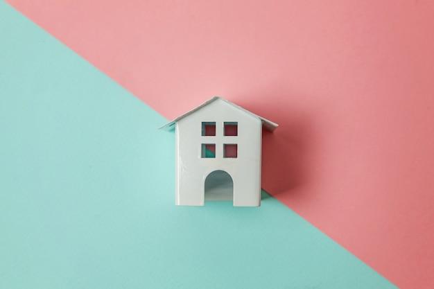 Casa de juguete blanco en miniatura sobre fondo pastel azul y rosa