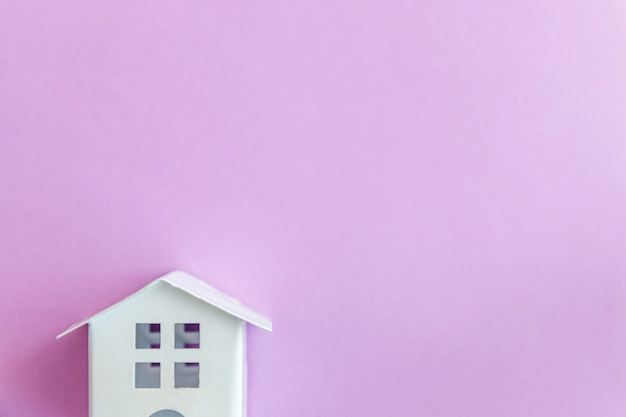 Casa de juguete blanco miniatura sobre fondo pastel violeta púrpura