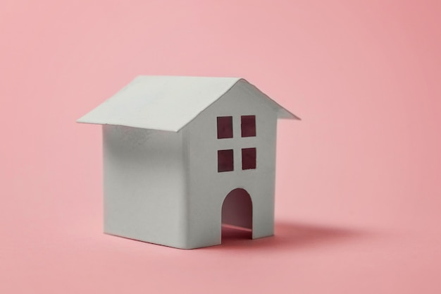 Casa de juguete blanco miniatura sobre fondo rosa