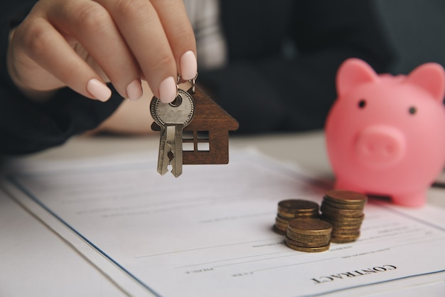 Casa de juguete de madera de cerca con la mujer firma un contrato de compra o hipoteca para una casa, concepto inmobiliario.