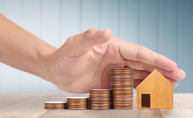 Casa de juguete de madera concepto de vivienda de propiedad hipotecaria compra para familia, monedas en mano
