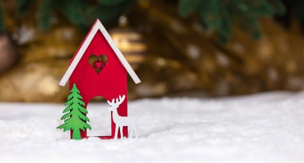 Casa de juguete de madera de navidad, ciervos y árboles sobre una manta blanca imitando la nieve.