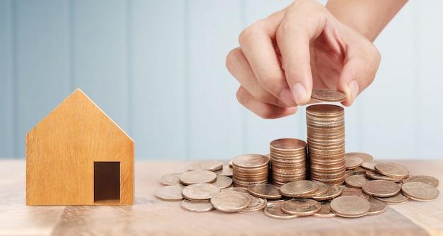 Casa de juguete de madera propiedad de hipoteca hogar compra para la familia, monedas en mano