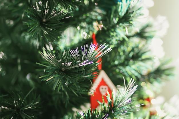 Casa de juguete de madera roja en las ramas de los árboles de navidad decorados