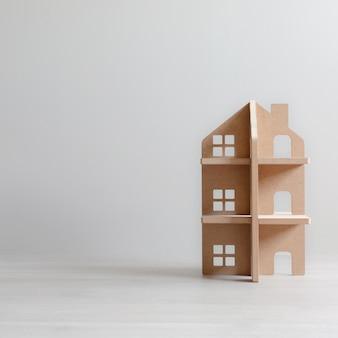 Casa de juguete de madera de tres pisos en habitación luminosa con espacio de copia.