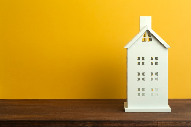 Casa de juguete sobre fondo amarillo. inmobiliaria, vivienda de alquiler y concepto de casa.