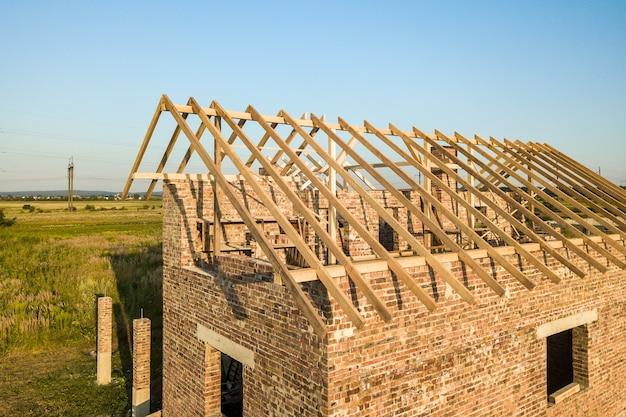 Casa de ladrillos sin terminar con estructura de techo de madera en construcción.