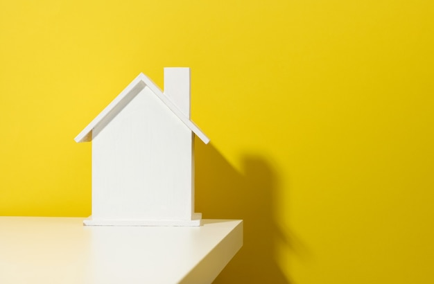 Casa de madera blanca sobre un fondo amarillo. concepto de alquiler, compra y venta de bienes raíces. servicios inmobiliarios, reparación y mantenimiento de edificios