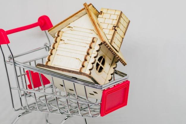Casa de madera en carrito de compras de juguete. concepto inmobiliario y financiero