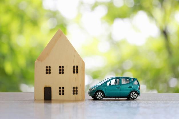 Casa de madera y coches de juguete en el suelo.