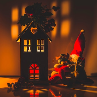 Casa de madera iluminada con muñecas de trapo.