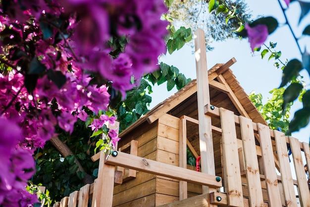 Casa de madera levantada para juegos de niños en un patio privado hecha con maderas ecológicas.