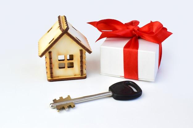 Casa de madera con llaves y caja de regalo.