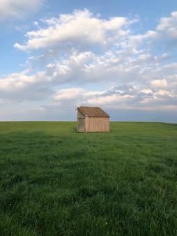 Casa de madera marrón en campo de hierba verde bajo nubes blancas durante el día