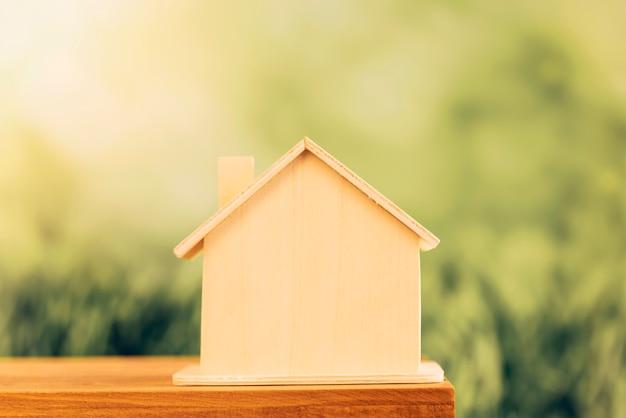 Casa de madera en miniatura en la mesa contra el fondo verde de desenfoque