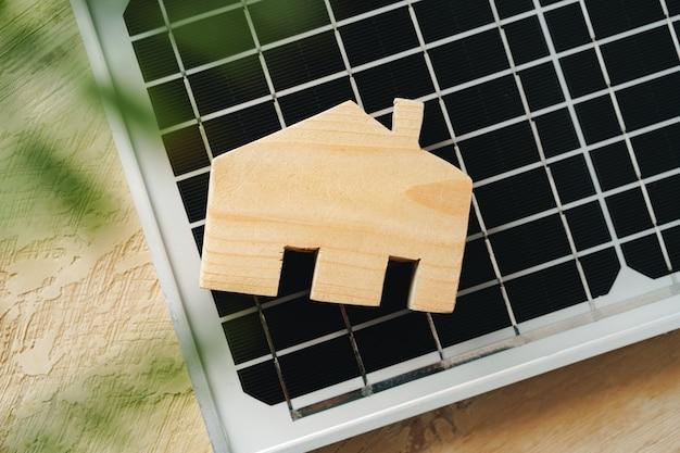 Casa de madera en miniatura y panel solar de cerca