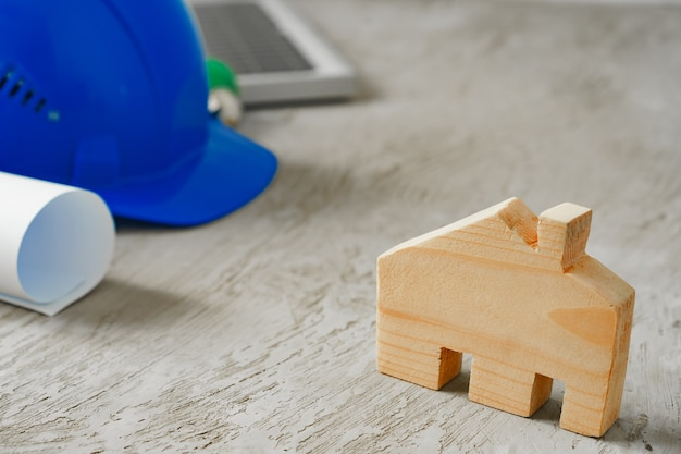 Casa de madera en miniatura y planos sobre mesa de madera