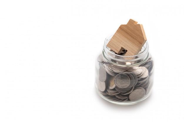Casa de madera modelada sobre muchas monedas en un frasco de vidrio